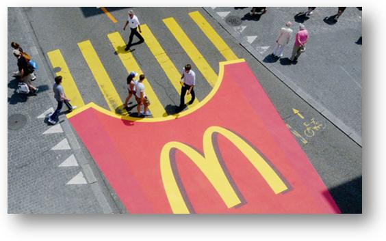 Een afbeelding van een zebrapad waarvan de strepen frietjes moeten voorstellen. Een voorbeeld van guerillamarketing van McDonalds.